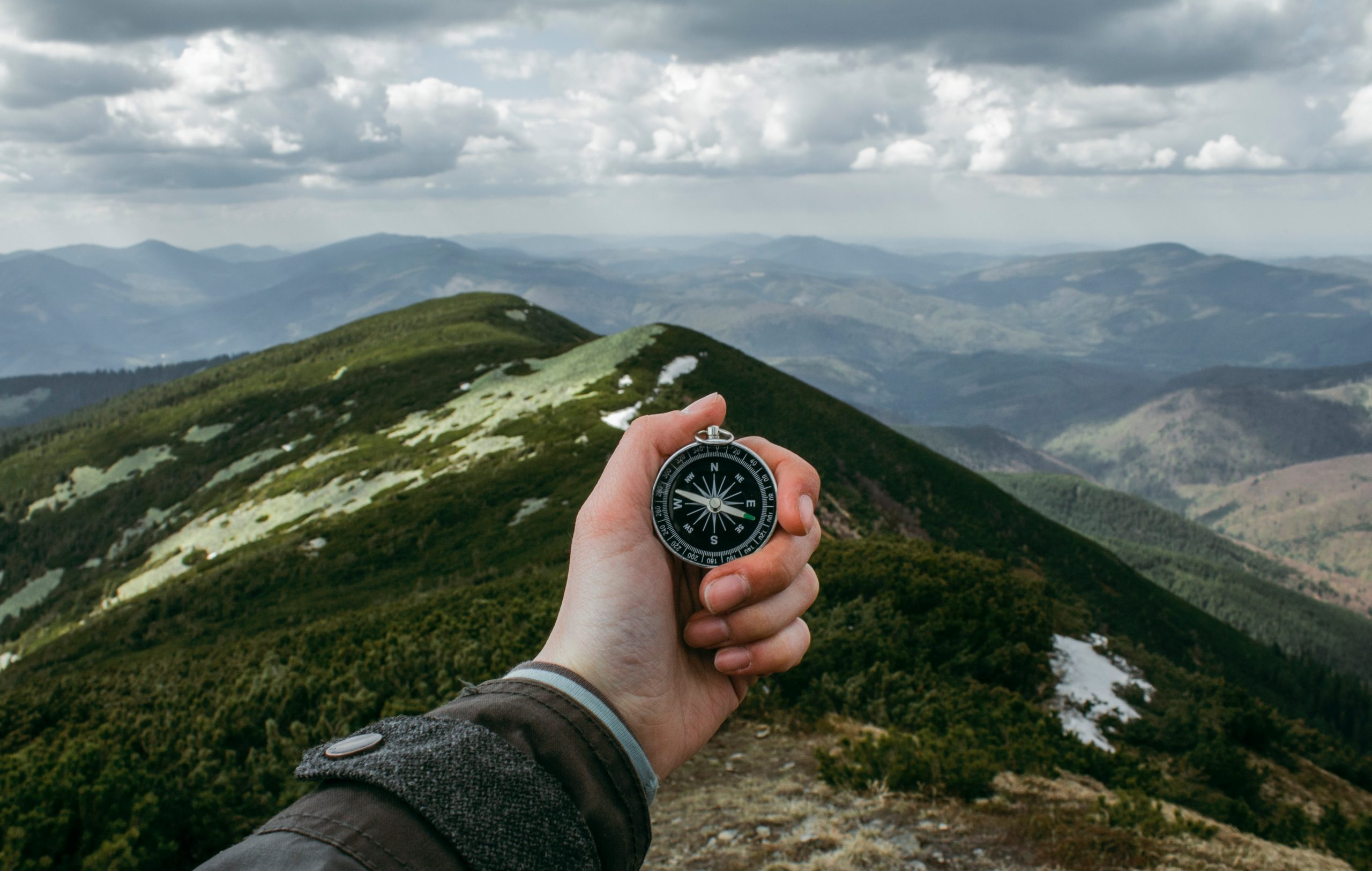 Hand holding a compass with green mountains in background