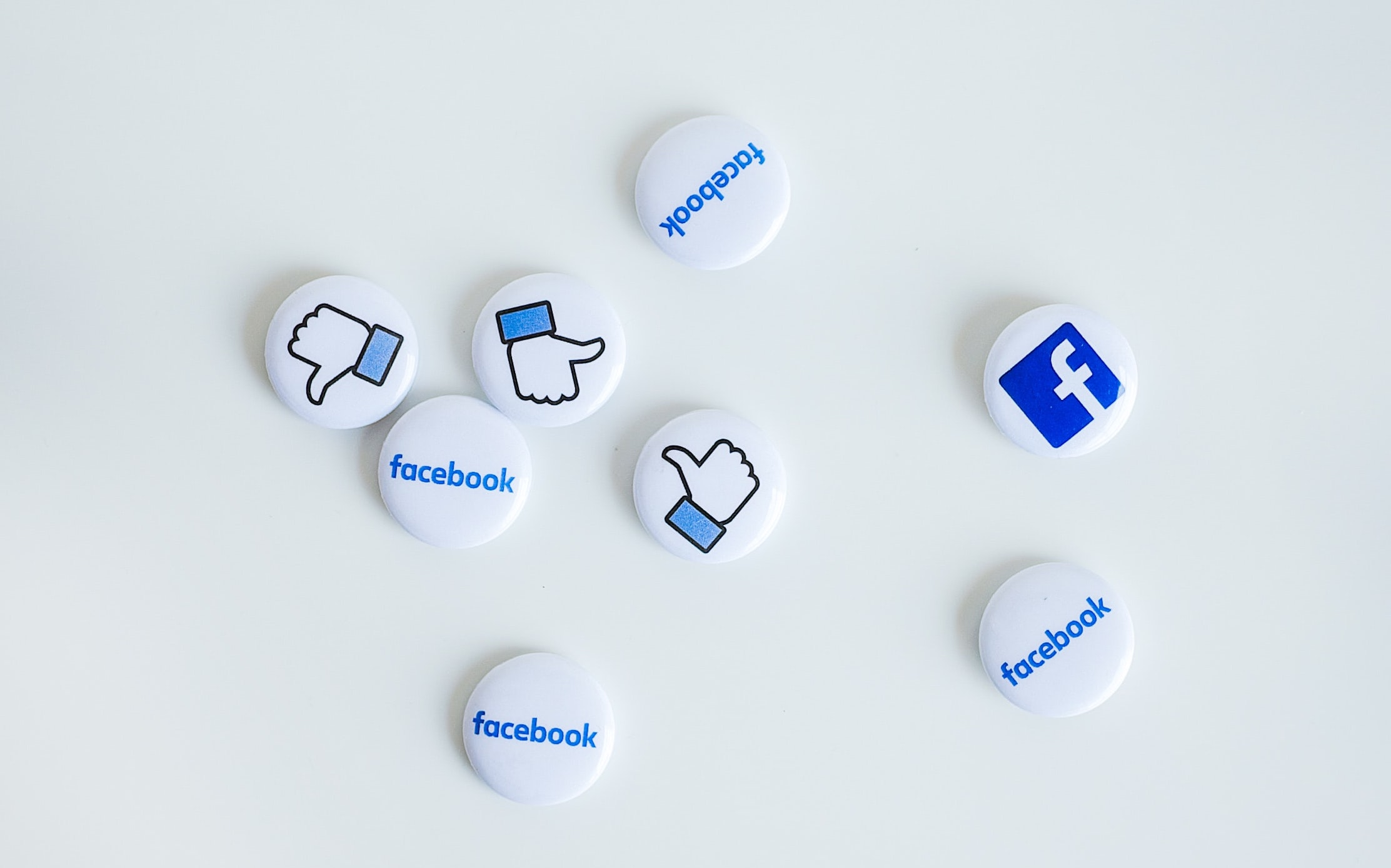 little badges on a table with facebook logos and like symbols